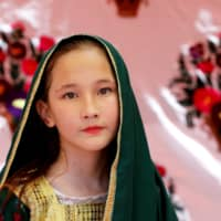 A Hazara girl poses during the Hazara Culture Day at the Qayum Papa Stadium in Quetta, Pakistan, on June 22. | REUTERS