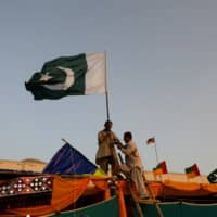 Men display the Pakistan national flag on a stall ahead of Hazara Culture Day celebrations. | REUTERS