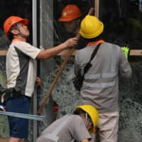 Workers repair windows of the Legislative Council building in Hong Kong on Wednesday that were damaged during a protest a day earlier.   AFP-JIJI