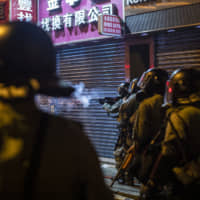 A riot police officer fires tear gas in the direction of demonstrators during a protest in the Sheung Wan district of Hong Kong on Sunday. | BLOOMBERG
