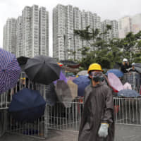 Protesters with wearing protective clothing use umbrellas and steel barricades in an effort to block a road during a march through Shatin, in  Hong Kong's New Territories, on Sunday.   AP