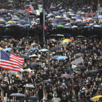 Protesters carry U.S. flags and placards during a protest march in Hong Kong on Sunday. A sea of black-shirted protesters, some with bright yellow helmets and masks but many with just backpacks, marched down a major street in central Hong Kong in the latest rally in what has become a summer of protest. | AP