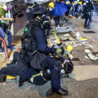 A police officer subdues demonstrators during a protest in Hong Kong on Sunday. | BLOOMBERG