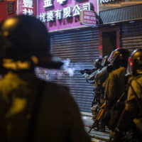 Riot police officers fire tear gas in the direction of demonstrators during a protest in the Sheung Wan district of Hong Kong on Sunday. | BLOOMBERG