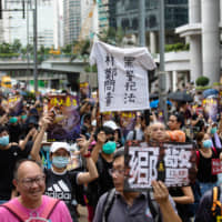 Demonstrators hold up signs while marching towards Causeway Bay during a protest in the Central district of Hong Kong on Sunday. | BLOOMBERG