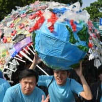 Indonesians protest against single-use plastics in Jakarta on July 21. Behind them is an anglerfish made out of plastic waste. | AFP-JIJI