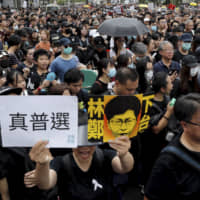 Protesters holding a caricature of Hong Kong Chief Executive Carrie Lam bearing the words 'Step down' and 'Real election,' take part in a march in Hong Kong on Sunday. | AP