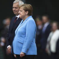 German Chancellor Angela Merkel and Prime Minister of Finland Antti Rinne listen to the national anthems at the chancellery in Berlin Wednesday. Merkel's body shook visibly as she stood alongside the Finnish prime minister and listened to the national anthems during the welcoming ceremony at the chancellery. | AP