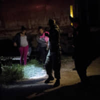 A Mexican immigration agent and police detain migrants during a raid on the cargo train known as 'La Bestia' in San Mateo, Chiapas state, Mexico, late  June 26. | AP