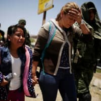 Members of Mexico's National Guard escort a woman and her daughter from Nicaragua after detaining them as they were trying to cross illegally the border between the U.S. and Mexico, in Ciudad Juarez, Mexico, June 21. | REUTERS