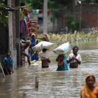 Indian residents wade along a flooded street carrying their belongings following heavy monsoon rains at the Sitamarhi district in the Indian state of Bihar on Wednesday. In India, the death toll rose to at least 120 and entire communities were cut off by rising floodwaters. | AFP-JIJI