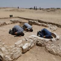 Muslim workers for the Israeli Antiquities Authority pray at the newly discovered remains of an ancient rural mosque in Rahat on July 18. | AFP-JIJI