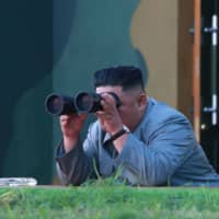 North Korean leader Kim Jong Un watches through binoculars as a short-range missile is launched at an undisclosed location in North Korea on Thursday. | AFP-JIJI