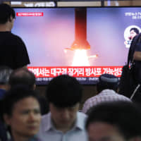 People watch a TV showing a file image of a North Korean missile launch during a news program at the main railway station in Seoul on Wednesday. | AP