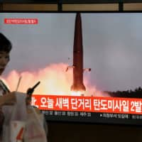 A woman walks past a television news screen showing file footage of a North Korean missile launch, at a railway station in Seoul on Wednesday. | AFP-JIJI