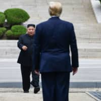 North Korean leader Kim Jong Un walks to greet U.S. President Donald Trump at the Military Demarcation Line that divides North and South Korea at the Joint Security Area in the truce village of Panmunjom at the Demilitarized Zone on June 30. | AFP-JIJI