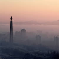 Morning fog blankets the 170-meter Juche Tower and other buildings in Pyongyang in September. | REUTERS