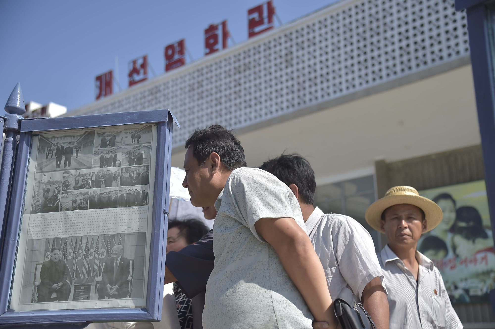 North Koreans read a newspaper carrying reports Sunday's meeting between U.S. President Donald Trump and their leader, Kim Jong Un, in Pyongyang on Monday. | AFP-JIJI