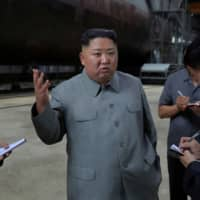 North Korean leader Kim Jong Un inspects a newly built submarine at an undisclosed location in this undated picture released Tuesday. | REUTERS