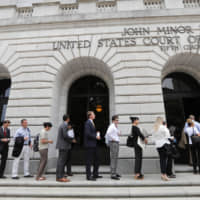 People wait to enter the 5th Circuit Court of Appeals to sit in overflow rooms to hear arguments in New Orleans Tuesday. The court will hear arguments on whether Congress effectively invalidated former President Barack Obama's entire signature health care law when it zeroed out the tax imposed on those who chose not to buy insurance. | AP