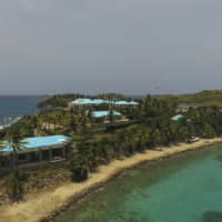 This July 9 video frame grab shows an aerial view of Little Saint James Island, in the U. S. Virgin Islands, a property purchased by Jeffery Epstein more than two decades ago. Epstein built on the island a stone mansion with cream-colored walls and a bright turquoise roof surrounded by several other structures, including the maids' quarters and a massive, square-shaped white building on one end of the island.