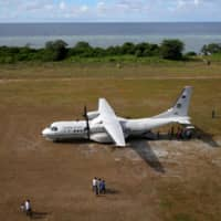 People walk towards a parked Philippine Air Force plane on the island of Thitu in the Spratly Islands in the disputed South China Sea in April 2017.   REUTERS
