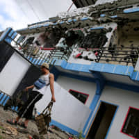 A member of the local security forces carries personal belongings past a bullet-riddled apartment house in a residential area in the Malutlut district of Marawi in the southern Philippines on Oct. 27, 2017. The building was believed to have been rented by pro-Islamic State militant group leaders Isnilon Hapilon and Omar Maute before their battle in the city. | REUTERS