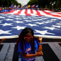 A girl helps carry a U.S. flag as she takes part in a parade during Fourth of July celebrations in Washington. | REUTERS