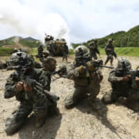 South Korean and U.S. Marines aim their machine guns during a joint military exercise between the two countries in Pohang, South Korea, in July 2016. | AP