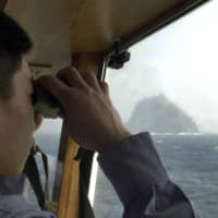 A member of the South Korean Coast Guard looks at the Takeshima islets, known in the South as Dokdo, aboard a patrol ship in the Sea of Japan in April 2005. South Korean jets fired warning shots after a Russian military plane violated South Korea's airspace on Tuesday, Seoul officials said, in the first such incident between the countries. | AP