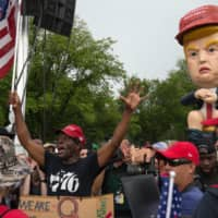 A pro-Trump supporter (left) protests in front of a statue of U.S. President Donald Trump tweeting on a toilet, at the National Mall ahead of the 'Salute to America' Fourth of July event with U.S. President Donald Trump at the Lincoln Memorial, at the National Mall in Washington Thursday.   AFP-JIJI
