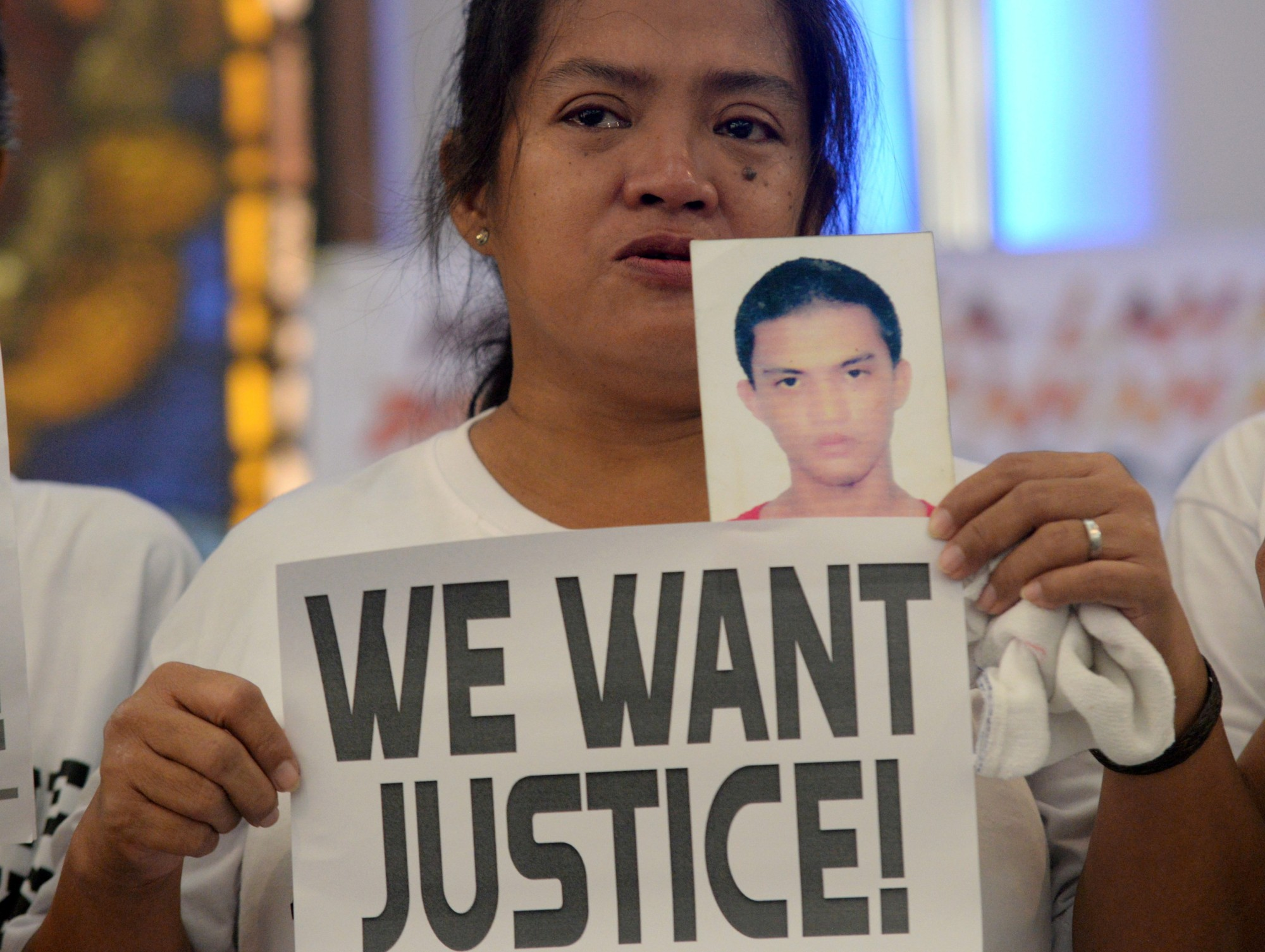A woman displays a picture of her son, a drug war victim, and a placard during a protest over the war on drugs by President Rodrigo Duterte in Quezon city, Metro Manila, Philippines, last August 28. | REUTERS