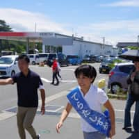 Shizuka Terata, an independent unofficially backed by four opposition parties in Akita Prefecture, runs toward voters in Kisakata on July 13. Akita's single-seat constituency is one of the highest-profile electoral districts for Sunday's Upper House vote.   REIJI YOSHIDA