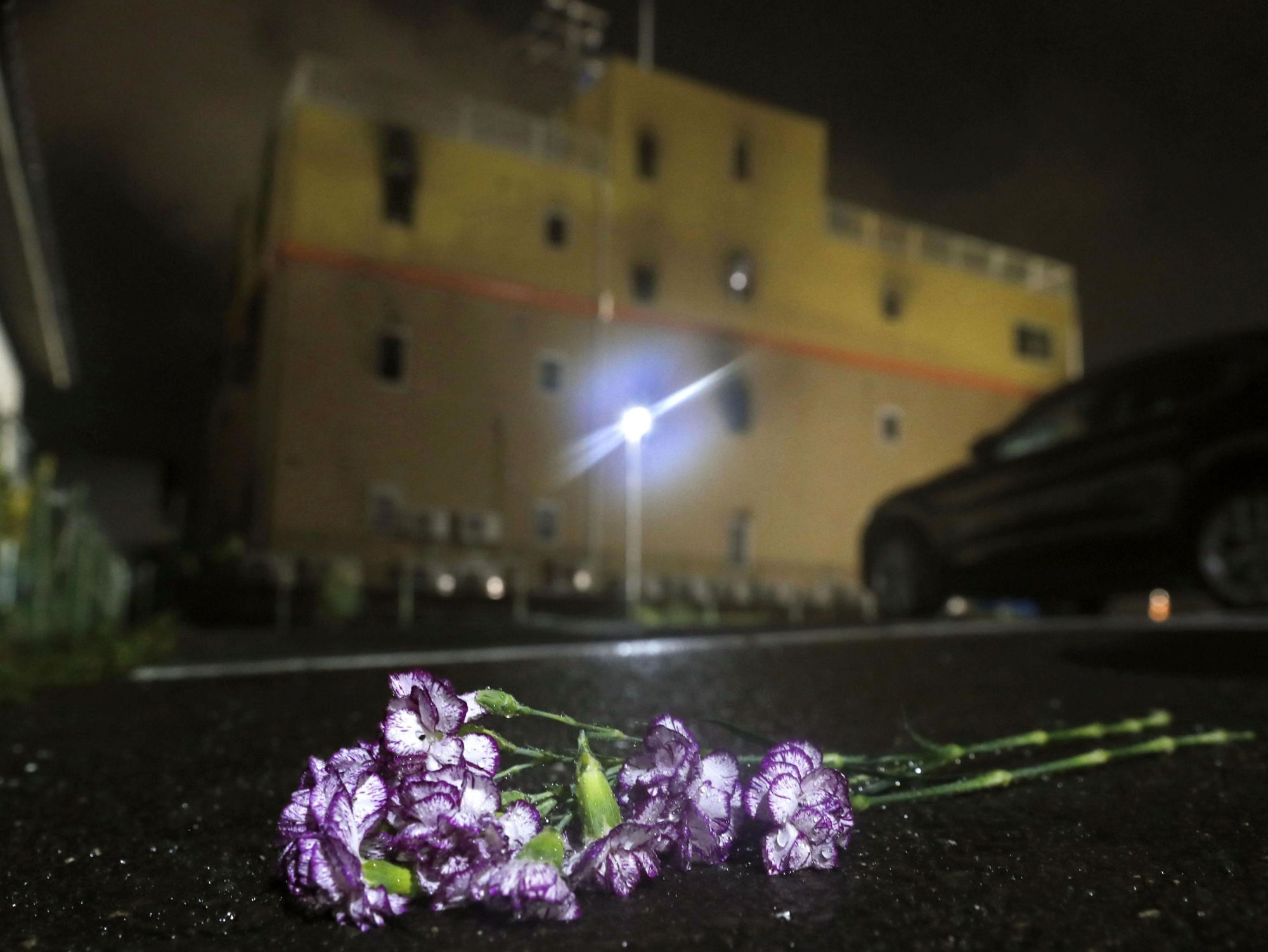 Flowers are laid in front of the Kyoto Animation Co. studio building in Kyoto's Fushimi Ward on Thursday after a suspected arson gutted the structure and killed at least 33 people and injured dozens of others.   KYODO