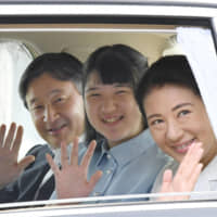 Then-Crown Prince Naruhito, Princess Aiko and then-Crown Princess Masako wave as they head to the Imperial Palace in Tokyo in July 2018. | POOL / VIA KYODO