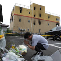 A man prays next to flowers and tributes laid at the scene Friday, where more than 30 people died in a fire at an animation company studio in the city of Kyoto. | AFP-JIJI