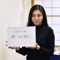 Rie Saito holds a board that reads 'Toward a town where people's minds can be heard' on March 29 at the Kita Ward Office in Tokyo. | KYODO