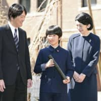 Prince Hisahito, along with his parents Crown Prince Akishino and Crown Princess Kiko,  attend a graduation ceremony at his Tokyo elementary school in March. | KYODO