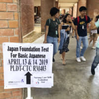 A sign directs test-takers toward a Japanese-language exam in Manila in April for those who want to work in Japan under a new visa category. Japan is planning to conduct language tests in other countries in the autumn. | KYODO