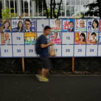 A man walks past election campaign posters for the Upper House election outside a voting station in Tokyo on Sunday. | REUTERS