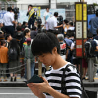 A man looks at his smartphone as a candidate for Sunday's Upper House election stumps on July 15 in Tokyo's Shibuya Ward. | YOSHIAKI MIURA