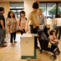 Voters cast their ballots at a polling station for the Upper House election in Tokyo on Sunday. | REUTERS