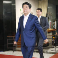 Prime Minister Shinzo Abe enters the headquarters of his Liberal Democratic Party in Tokyo on Sunday. | KYODO