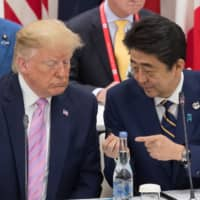 Prime Minister Shinzo Abe talks to U.S. President Donald Trump as they attend a meeting on the digital economy at the Group of 20 Summit in Osaka on Friday. | AFP-JIJI