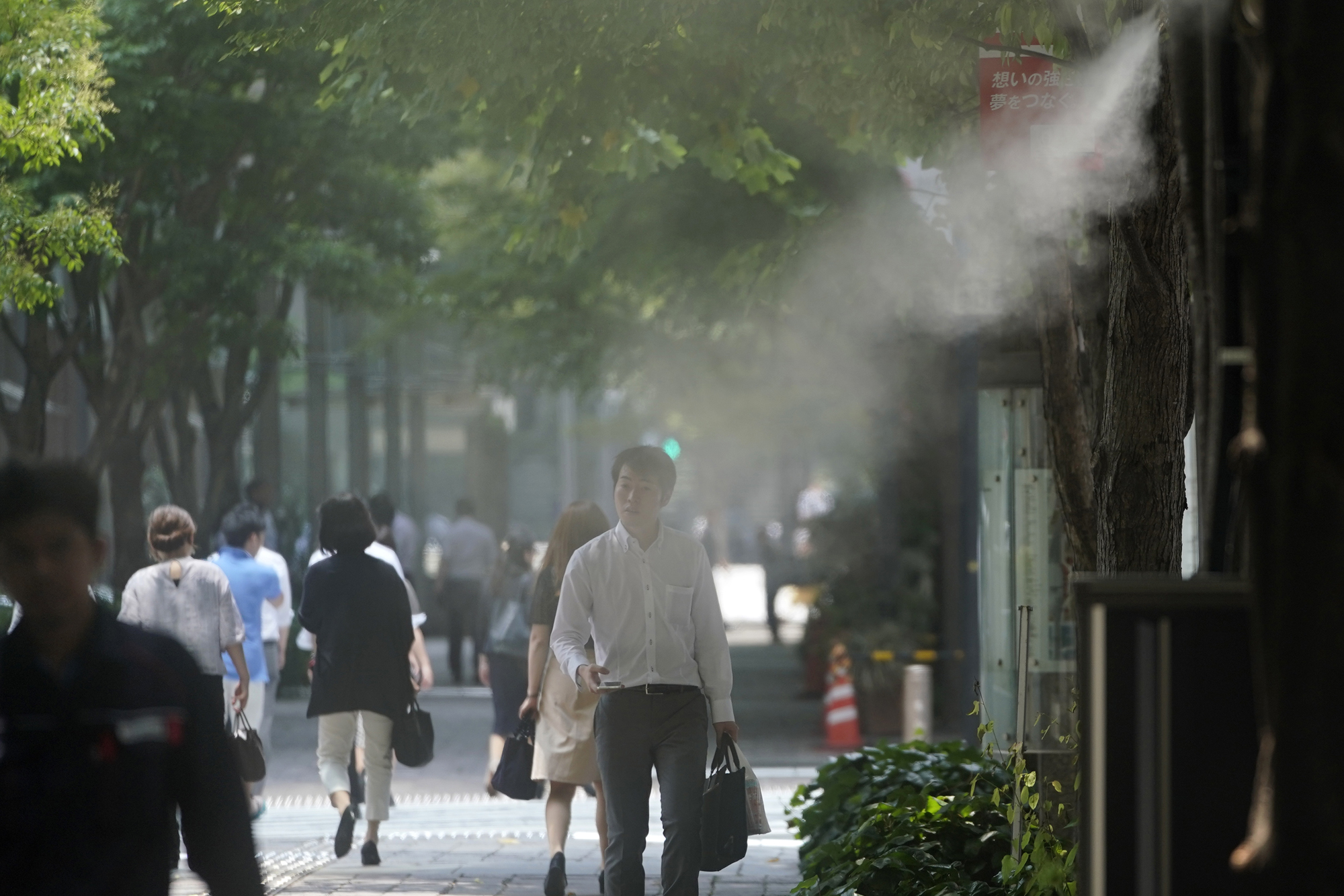 A pedestrian walks under a mist cooling system in the Otemachi business district in Tokyo on Monday. After temperatures spiked in many areas following the end of the rainy season, there have been reports of deaths and hospitalizations due to heat-related medical issues across the country. The Meteorological Agency said temperatures were expected to remain above average in the upcoming week. | BLOOMBERG