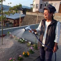 Yukie Kirioka, who lost her husband last year in a mudslide triggered by heavy rains, waters her flowers at a place where her house used to stand in the town of Kumano, Hiroshima Prefecture. | CHUGOKU SHIMBUN