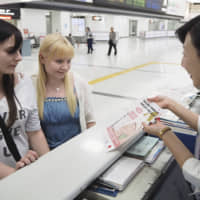 Tourists receive an explanation about travel insurance at Narita airport on May 23. | KYODO