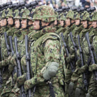 Members of the Self-Defense Forces march during a review at Ground Self-Defense Force Camp Asaka in Saitama Prefecture in October 2018. | BLOOMBERG