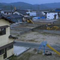 Vacant lots are seen in the Mabicho district of Kurashiki, Okayama Prefecture, on Saturday. Many houses that were damaged in last year's flooding were pulled down. | KYODO