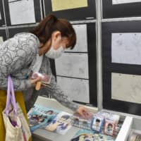 A woman on Tuesday visits an exhibit in Tokushima of original artworks produced by Kyoto Animation Co., whose studio was hit by an arson attack last week that left 34 people dead. | KYODO